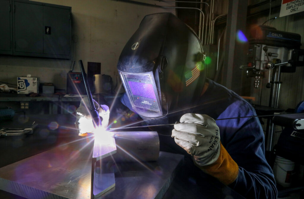 person welding with futuristic looking face shield