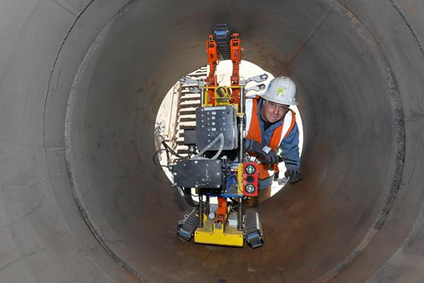 employee metering the inside of a pipeline