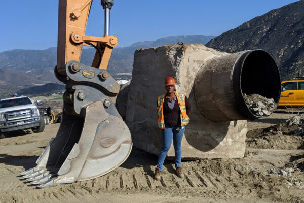 worker standing in front of digger arm and pipeline being built