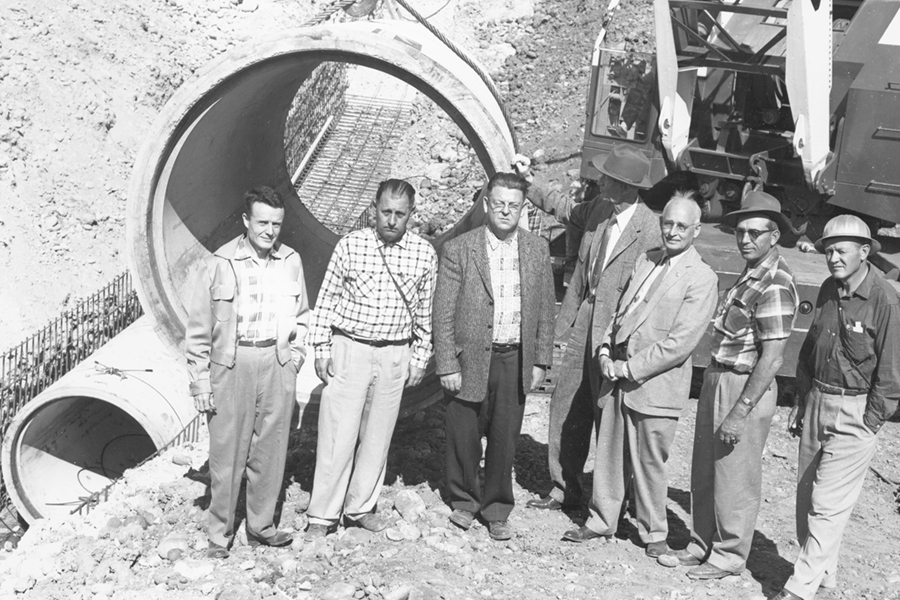 men standing in front of pipeline 3 for a picture