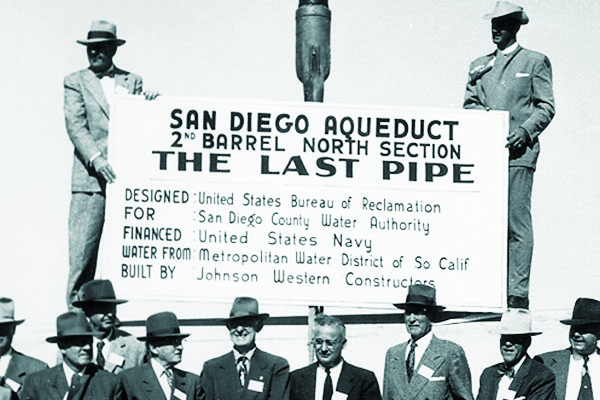 two men holding up a sign commemorating the last barrel in a pipeline being laid